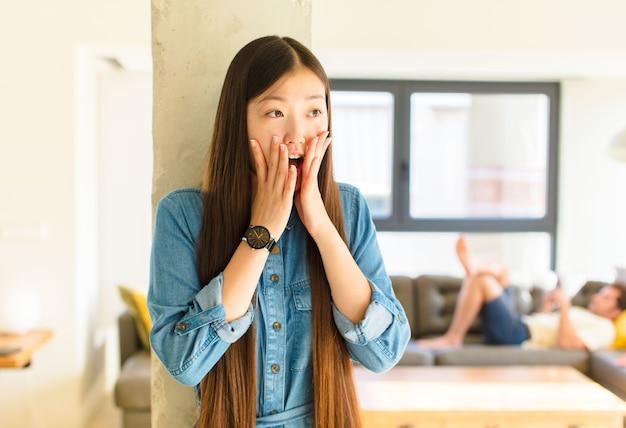 幸せ、興奮、驚きを感じ、顔を両手で横に見ている若いかなりアジアの女性