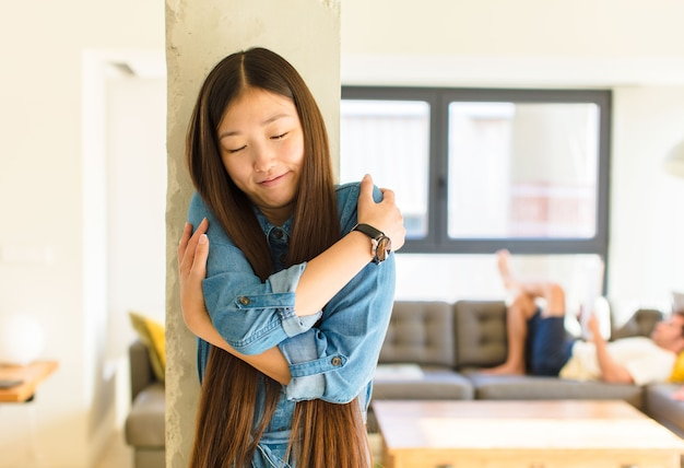 Young pretty asian woman feeling in love, smiling, cuddling and hugging self, staying single, being selfish and egocentric
