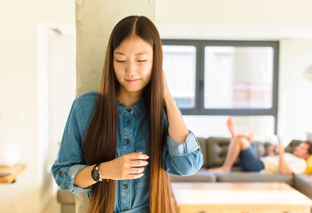 ストレス、欲求不満、疲れを感じ、痛みを伴う首をこすり、心配し、問題を抱えた表情で若いかなりアジアの女性
