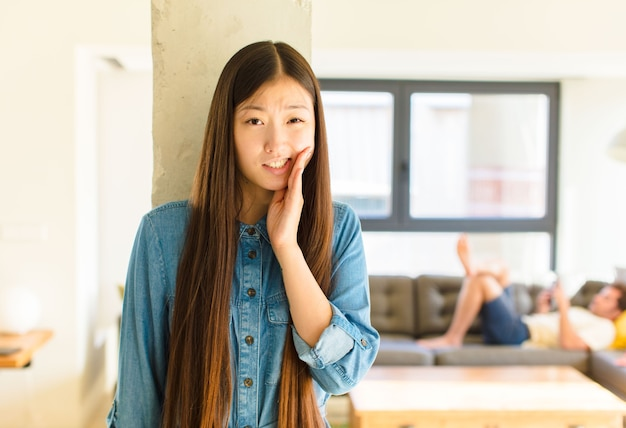 Young pretty asian woman holding cheek and suffering painful toothache, feeling ill, miserable and unhappy, looking for a dentist