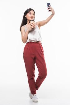 Молодая милая азиатская женщина держа кофе и принимает selfie над белой стеной