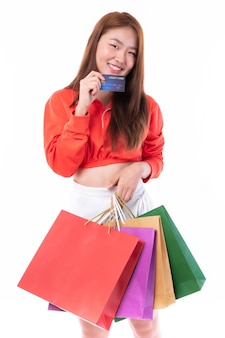 Young pretty asian woman holding many shopping bag  and showing credit card for payment shopping on white background