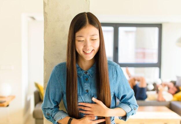 いくつかの陽気な冗談で大声で笑って、幸せで陽気に感じて、楽しんでいる若いかなりアジアの女性