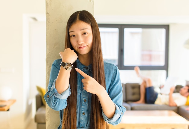 Young pretty asian woman looking impatient and angry, pointing at watch, asking for punctuality, wants to be on time