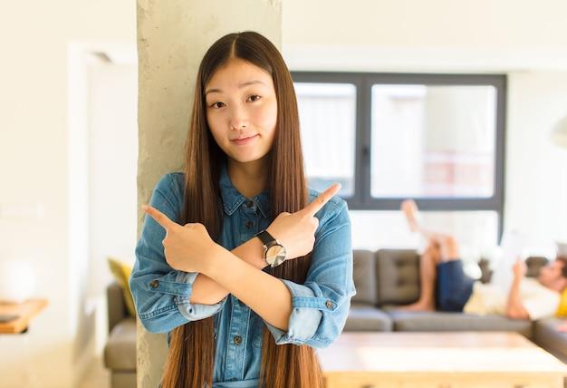 Молодая симпатичная азиатская женщина выглядит озадаченной и сбитой с толку, неуверенной и с сомнениями указывает в противоположные стороны