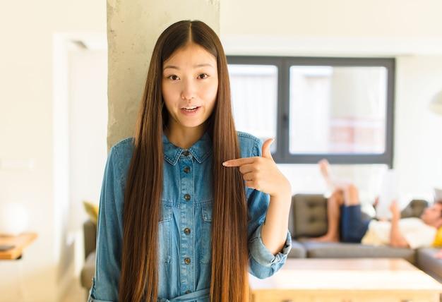 自分を指して、口を大きく開いてショックを受けて驚いたように見える若いかなりアジアの女性