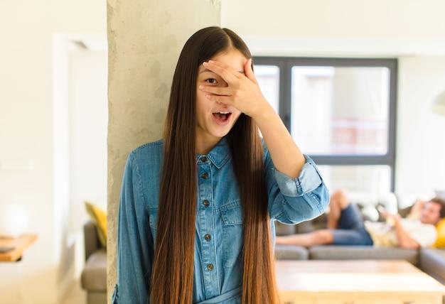 Молодая симпатичная азиатская женщина выглядит шокированной, напуганной или напуганной, закрывает лицо рукой и смотрит между пальцами