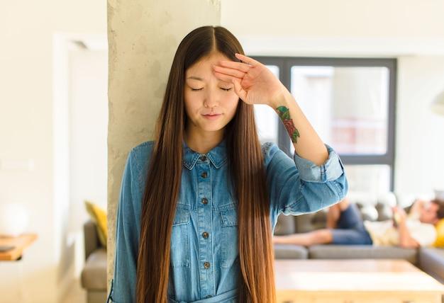 Молодая симпатичная азиатская женщина выглядит напряженной, уставшей и расстроенной, вытирает пот со лба, чувствует себя безнадежной и истощенной