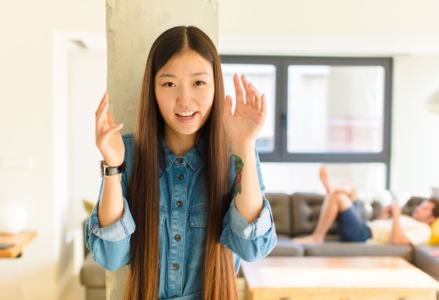 Young pretty asian woman screaming in panic or anger, shocked, terrified or furious, with hands next to head