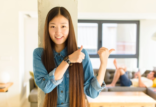 Young pretty asian woman smiling cheerfully and casually pointing to copy space on the side, feeling happy and satisfied