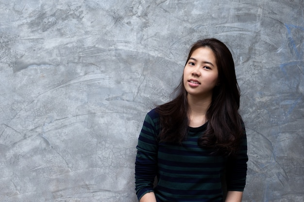 Young pretty asian woman smiling in grey concrete wall background.