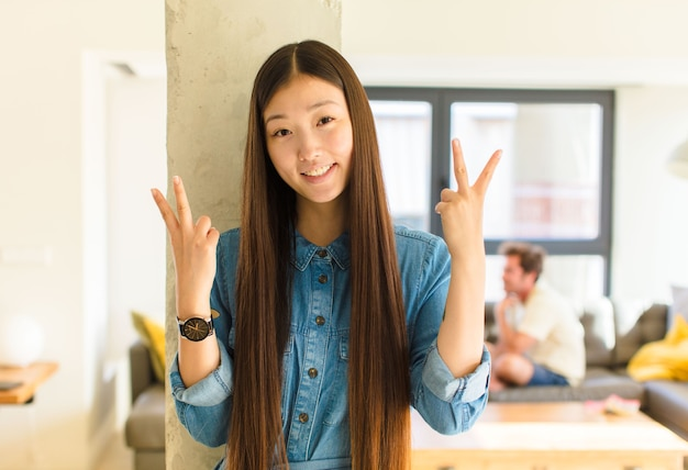 Young pretty asian woman smiling and looking happy, friendly and satisfied, gesturing victory or peace with both hands