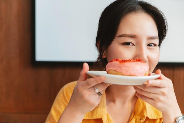 モダンなカフェで幸せな気分でストロベリーピンクドーナツのプレートを保持していると示す黄色のシャツを着ている若いかなりアジアの女性。