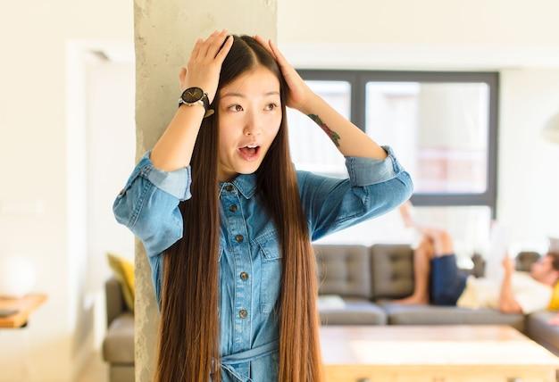Молодая симпатичная азиатская женщина с открытым ртом, выглядящая испуганной и шокированной из-за ужасной ошибки, поднимает руки к голове