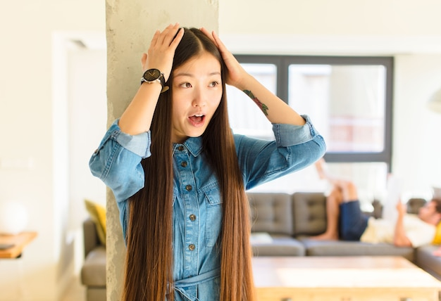Young pretty asian woman with open mouth, looking horrified and shocked because of a terrible mistake, raising hands to head