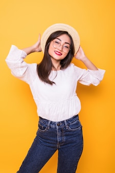 노란 벽에 고립 밀 짚 모자와 함께 젊은 꽤 아시아 여자