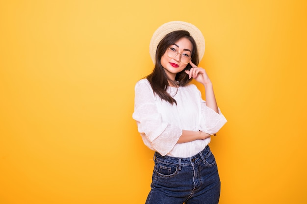 Young pretty asian woman with straw hat isolated on yellow wall