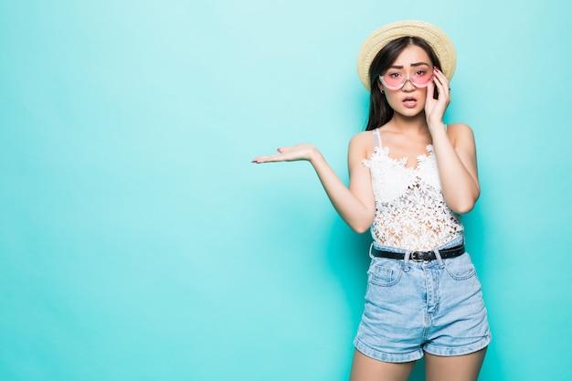 선글라스 제스처 오픈 팜 녹색 벽에 고립 된 젊은 꽤 아시아 여자