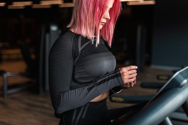Молодая симпатичная спортивная женщина в черной спортивной одежде достает наушники и готовится к пробежке на беговой дорожке в тренажерном зале