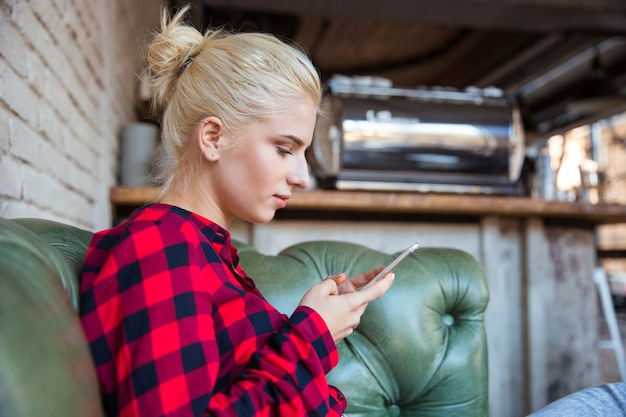 Young pretty attractive concentrated woman in checkred shirt sitting in cafe on green leather sofa and using mobile phone