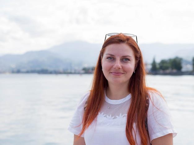 Молодая довольно привлекательная женщина с рыжими волосами смотрит на прогулку у моря, солнечный яркий летний день