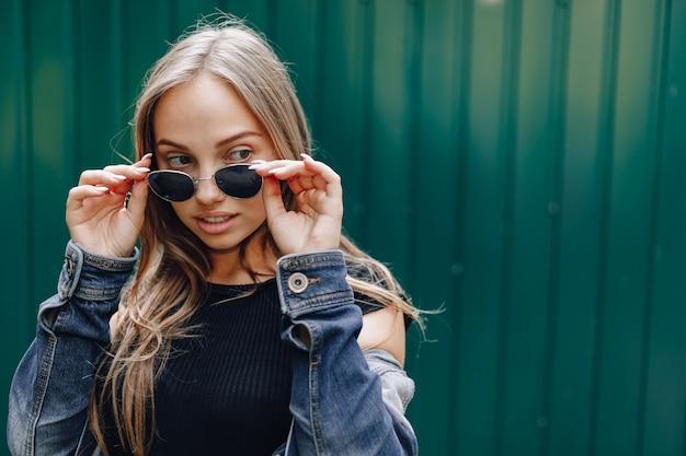 Giovane ragazza abbastanza attraente in vestiti di jeans in bicchieri su un semplice sfondo verde scuro con un posto vuoto per il testo