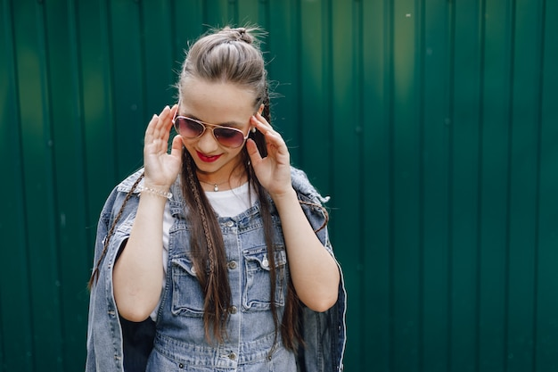 Young pretty attractive girl in denim clothes in glasses on a simple dark green wall with place for text.