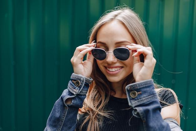 テキストのための空の場所とシンプルな濃い緑色の背景にメガネのデニムの服を着た若いかなり魅力的な女の子