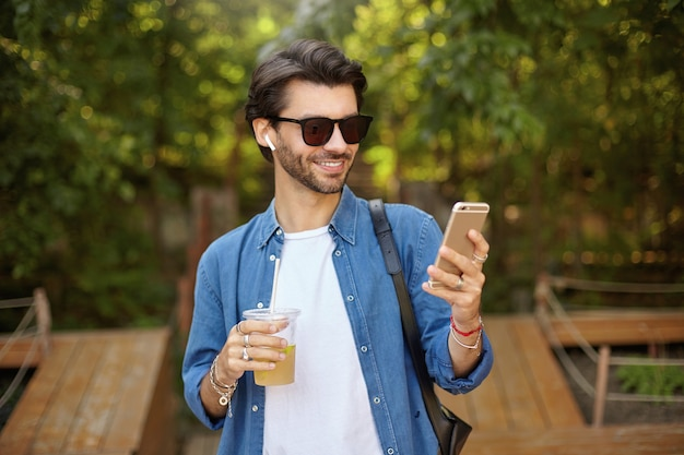 Young pretty bearded male with dark hair walking through green city garden, drinking lemonade and holding mobile phone in hand, looking at screen and smiling cheerfully