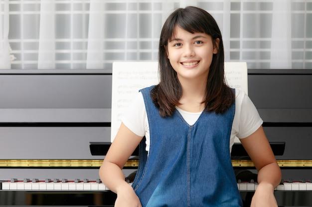 ぼやけた楽譜とメトロノーム、リズム機器でピアノに座っている若いかなり美しいアジアの女の子