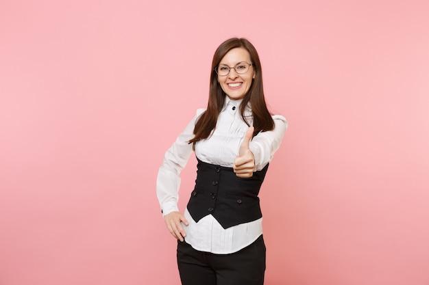 Молодая довольно красивая успешная бизнес-леди в черном костюме, очках показывает палец вверх, изолированные на пастельно-розовом фоне. леди босс. концепция богатства карьеры достижения. скопируйте место для рекламы.