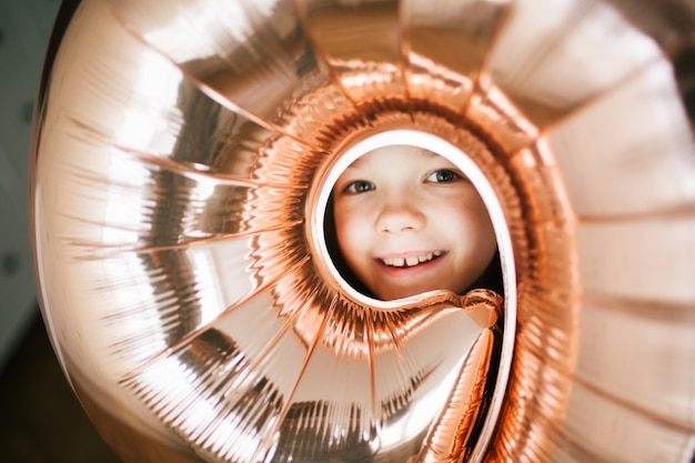 Young pretty birthday girl's face through the hole in the balloon