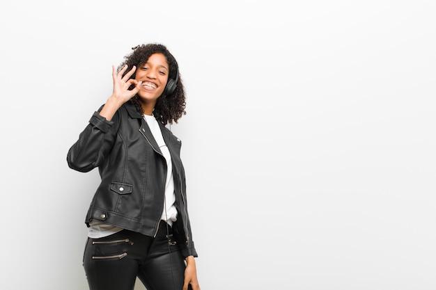 革のジャケットの白い壁を身に着けているヘッドフォンで音楽を聴く若いかなり黒人女性