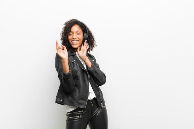 Young pretty black woman listening music with a headphones wearing a leather jacket against white