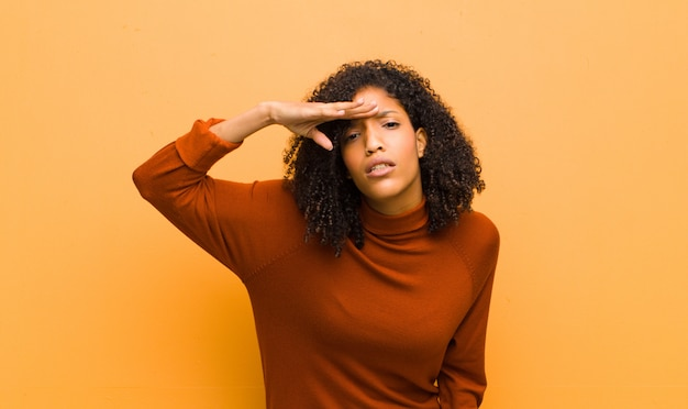 Young pretty black woman looking bewildered and astonished, with hand over forehead looking far away, watching or searching against orange wall