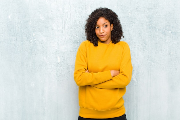 팔을 의심하고 혼란스러워하고 혼란스럽고 불확실한 젊은 예쁜 흑인 여성
