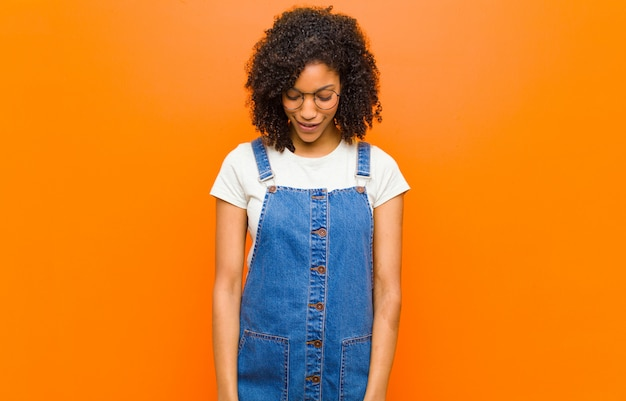 Young pretty black woman smiling cheerfully and casually, looking downwards and pointing to chest against orange wall