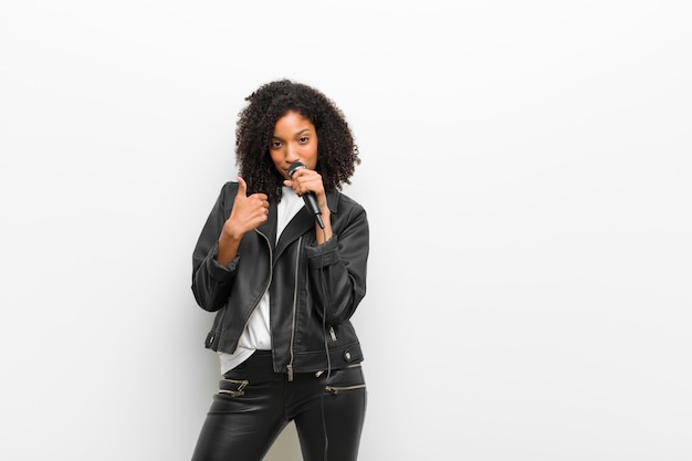 흰 벽에 가죽 재킷을 입고 마이크와 젊은 예쁜 흑인 여성
