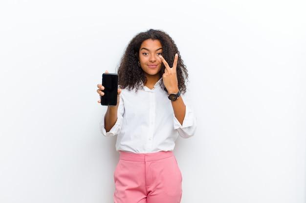 Молодая милая чернокожая женщина с умным телефоном против белой стены