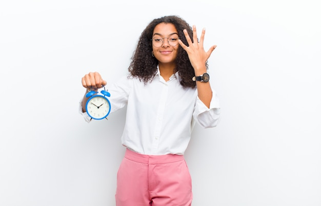 Young pretty black woman with an alarm clock against white wall