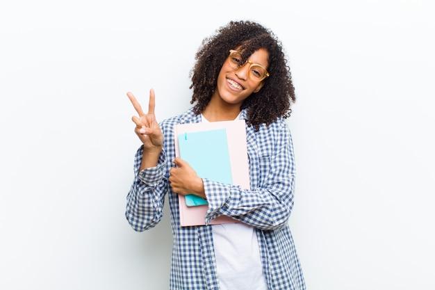 Молодая милая чернокожая женщина с книгами против белой стены