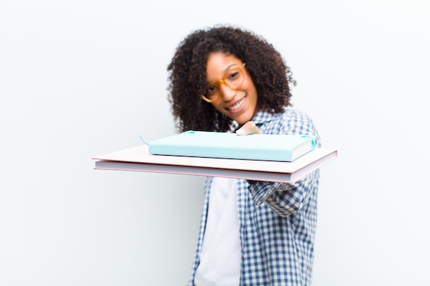 Young pretty black woman with books against white wall