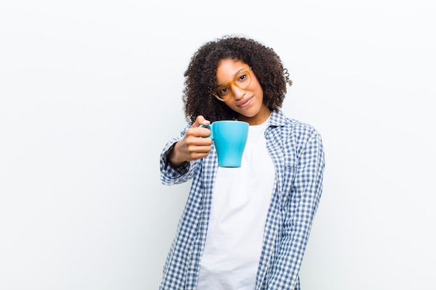 Young pretty black woman with a coffee  white wall