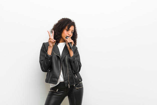 Young pretty black woman with a microphone wearing a leather jacket against white wall