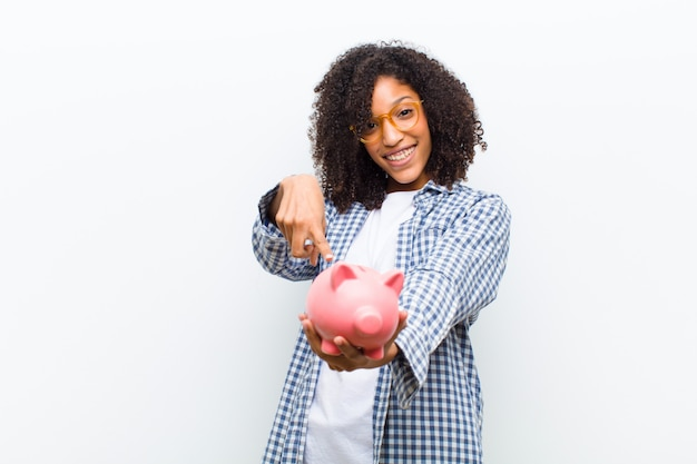Young pretty black woman with a piggy bank