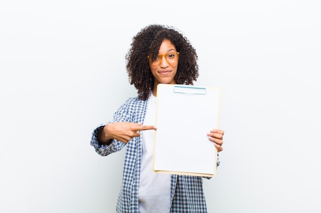 Young pretty black woman with a sheet of paper against white wall