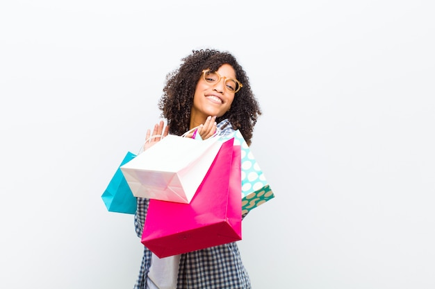 Young pretty black woman with shopping bags against white wall