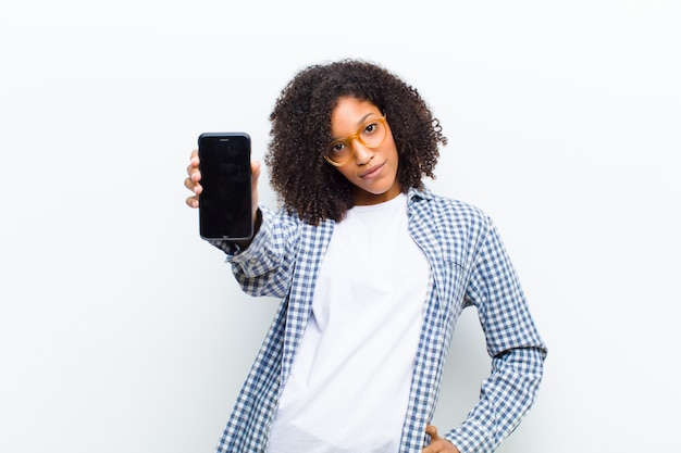 Young pretty black woman with a smart phone against white wall