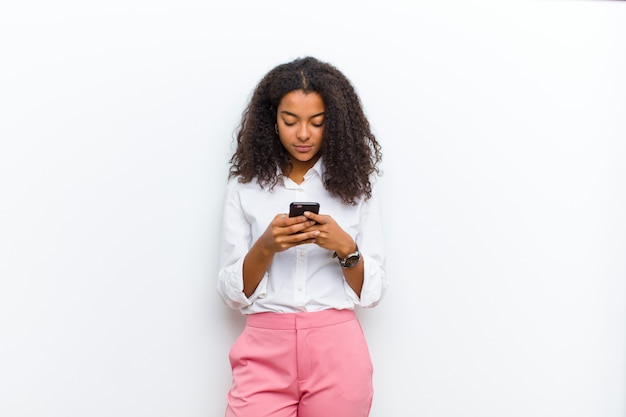 Young pretty black woman with a smart telephone against white wall