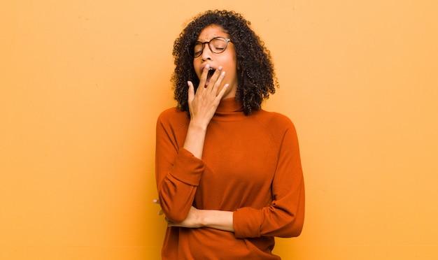 Молодая красивая чернокожая женщина лениво зевает рано утром, просыпается и выглядит сонной, уставшей и скучающей на оранжевой стене